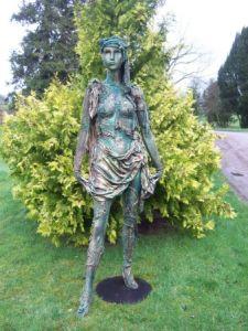 Estatua de uma mulher coberta de itens da natureza