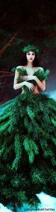 Foto de uma mulher vestida com ramos de pinheiro